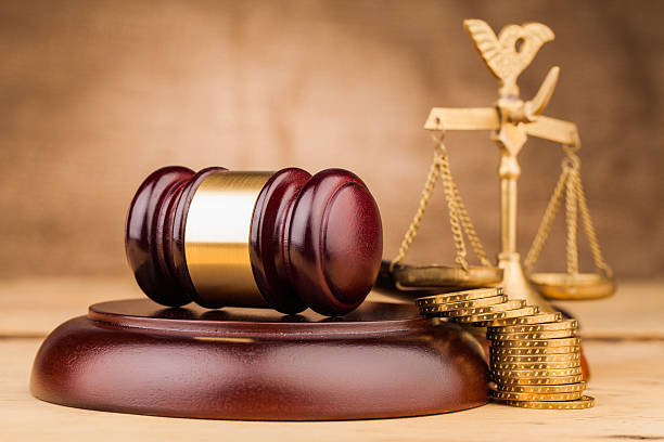 judge gavel  coins and scales on wooden table